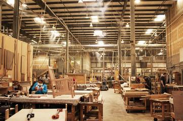 Carpenters working at illuminated workshop