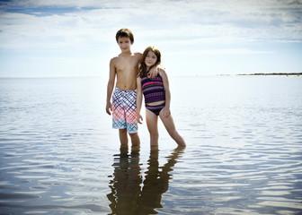 Girl and boy in swimwear standing in water