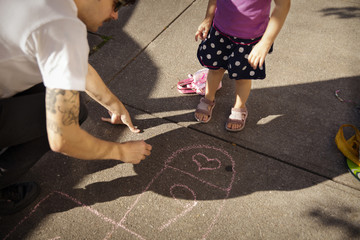 High angle view of father with daughter drawing on footpath