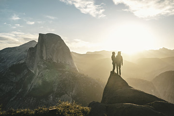 Young couple looking at sunset in mountains