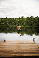 Rear view of boy jumping from wooden dock into lake