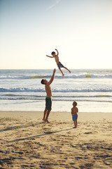 Boy looking at father playing with son while standing on shore at beach