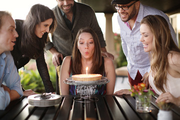 Woman blowing birthday candles with friends