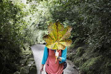 Woman covering face with large leaf