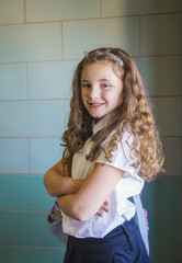 Portrait of girl with arms crossed standing in corridor