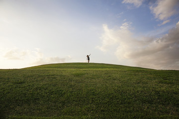 Silhouette of woman on hill in distance