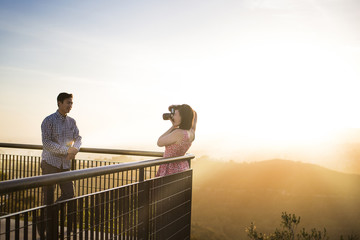 Woman photographing boyfriend while standing by railing against sky