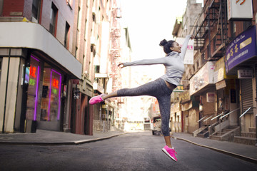 Young woman jumping on street