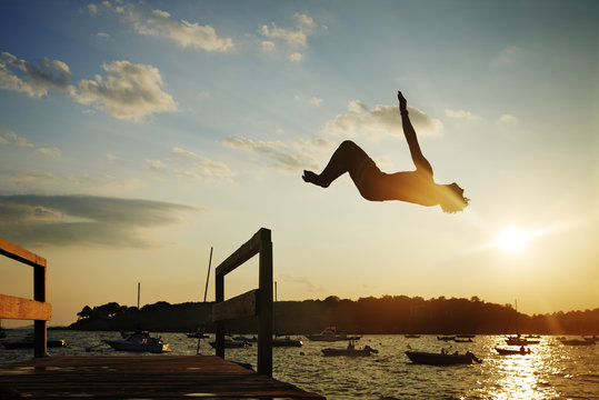 USA, Massachusetts, Magnolia, Silhouette of young man jumping into water at sunset