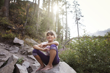 Girl resting on boulder in forest