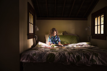 Girl reading book while sitting on bed in cabin