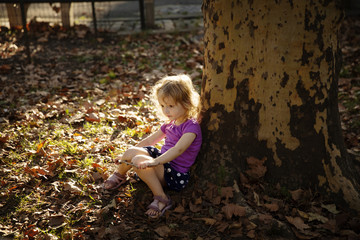 Cute girl sitting by tree trunk on field at park