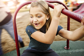 Happy girl playing on merry-go-round at park