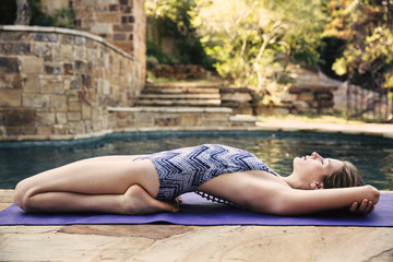 Side view of woman exercising near swimming pool