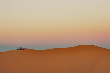 Sand buggy on sand dune at sunset