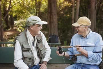 Smiling senior men sitting with fishing rod
