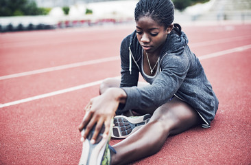 Young woman stretching leg on track