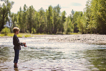 Young boy fishing in river