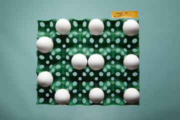 Eggs in carton on blue background