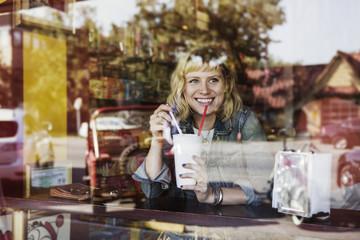 Woman behind window drinking milkshake