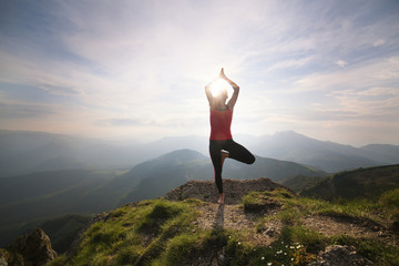 Woman practicing yoga on the mountain top