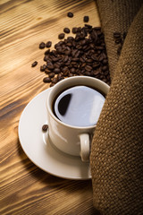 Coffee beans and coffee in white cup on wooden table with burlap