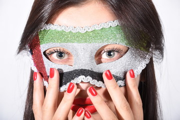 Girl wearing UAE flag mask showing red nails