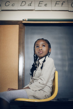 Thoughtful girl sitting on the yellow chair in the classroom