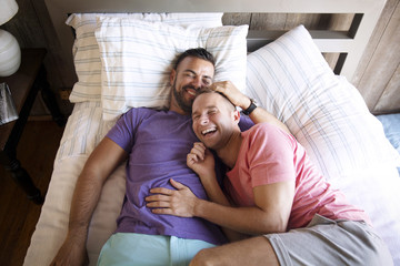 Happy homosexual couple lying on bed at resort