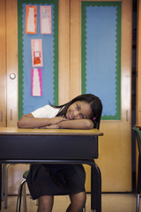 Portrait of girl sitting at desk in classroom