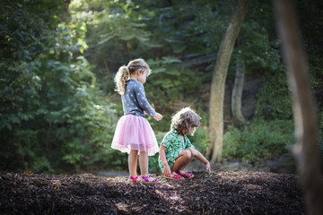 Girls (2-3, 4-5) looking at leaf in forest