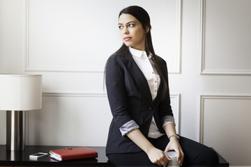 Businesswoman with mug looking away while sitting on table in office