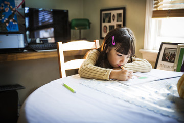 Girl drawing on book while sitting at table