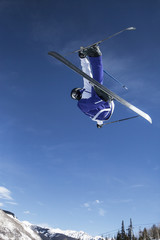 Low angle view of skier in mid-air against blue sky