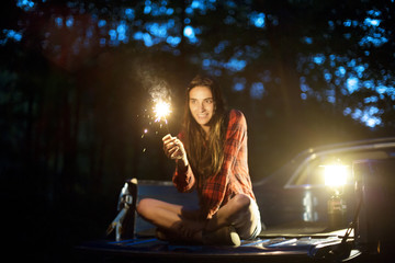 Young woman sitting on back of pick-up truck and holding sparkler