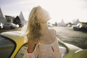 Young woman standing by car at sunset