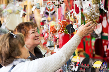Happy mature women purchasing Christmas decorations