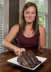 Woman Reaching for Slice of Chocolate Cake