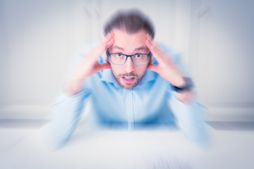 Businessman under stress sitting at the desk in the office with hands on his head. Business emotions and modern life concepts.