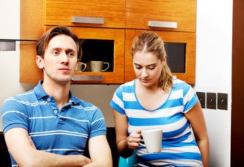 Young unhappy couple after quarrel in kitchen