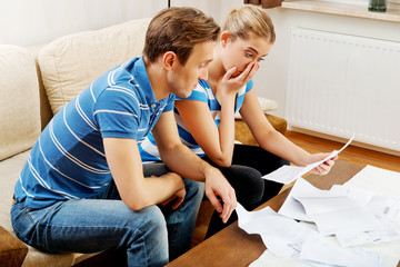 Worried couple calculating bills at home