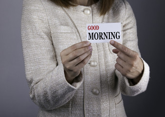 Good Morning. Businesswoman holding a card with a message text w