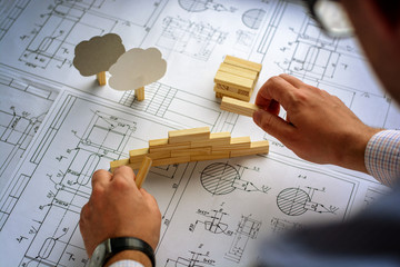Man architect draws a plan, graph, design, geometric shapes by pencil on large sheet of paper at office desk and builds model house from wooden blocks (bars)