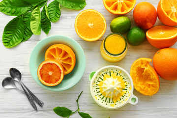 Eating oranges with spoon on white wooden background