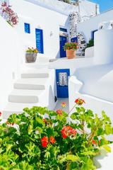 Obraz Traditional cycladic whitewashed architecture with blue doors and flower pots, Imerovigli, Santorini island, Greece - fototapety do salonu