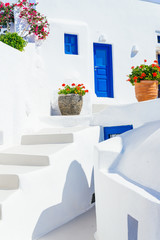 Traditional cycladic whitewashed architecture with blue doors and flower pots, Imerovigli, Santorini island, Greece