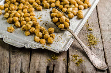 Roasted spicy chickpeas with zaatar or zatar on vintage metall try and wooden background. Top view