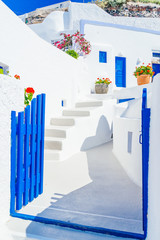 Traditional architectural detail of Santorini street with whitewashed streets and blue gates, Greece