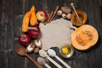 Ingredients for pumpkin and apple pie. Apples, nuts, pumpkin, honey, flour, eggs, oatmeal, sugar on vintage wooden background.