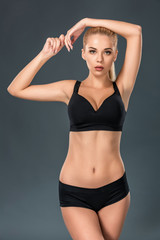 Young beautiful woman in fitness wear trained female body
